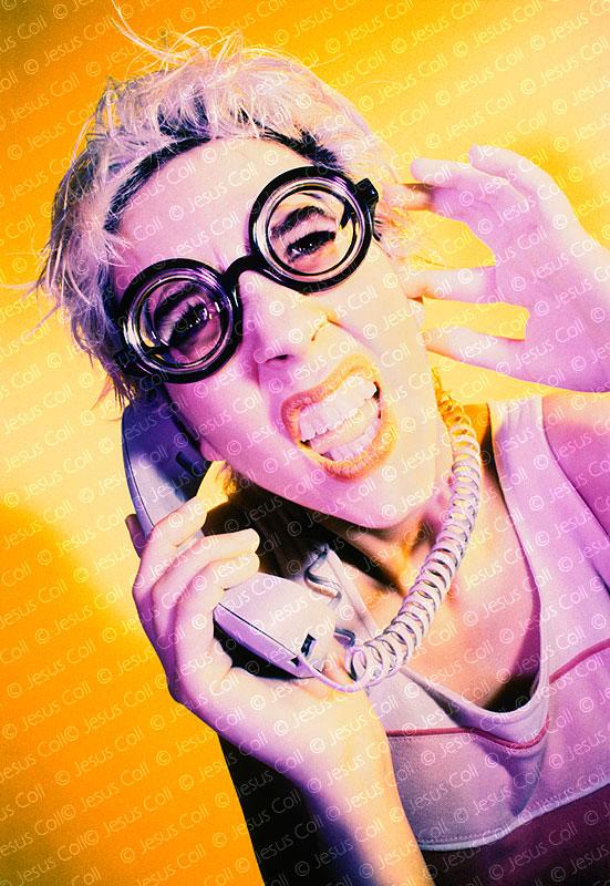 Mujer joven haciendo muecas mientras habla por teléfono. Fotografía de stock de Jesús Coll