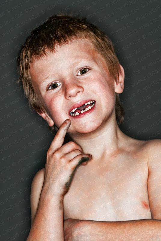 Niño mostrando el hueco de sus dos dientes caídas. Photografía de stock de Jesús Coll