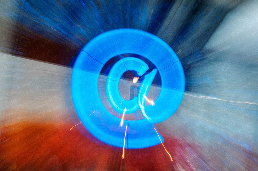 Signo arroba azul en neon efecto zoom, fotografía de stock de Jesus Coll.